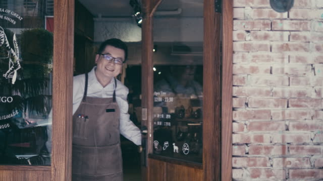 friendly asian male manager opens shoe shop door and welcomes new customers - open stock videos & royalty-free footage