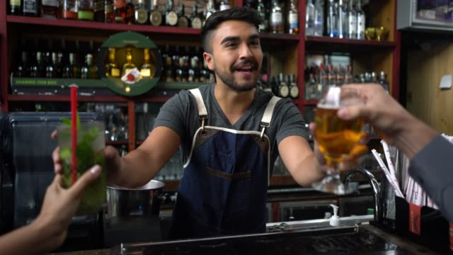 friendly bar tender serving drinks to an unrecognisable couple sitting at the bar counter - bartender stock videos and b-roll footage