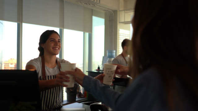 friendly barista handing take out coffee for customer couple at a coworking office - commercial kitchen stock videos & royalty-free footage