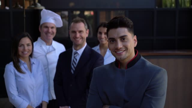 friendly bellhop facing camera with arms crossed and the rest of the hotel team standing at the background smiling - arms crossed stock videos & royalty-free footage