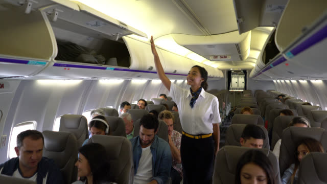 friendly black air stewardess closing over head compartments at a commercial flight - vehicle interior stock videos & royalty-free footage
