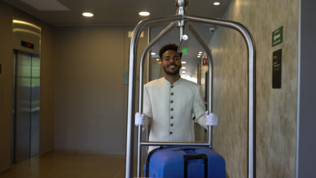 vídeos de stock e filmes b-roll de friendly black bellhop pushing luggage cart to the lobby while a customer is checking out - hotel