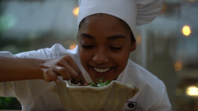 vídeos y material grabado en eventos de stock de amable chef negro añadiendo un toque final a una ensalada mientras se enfrenta a la cámara sonriendo - chef