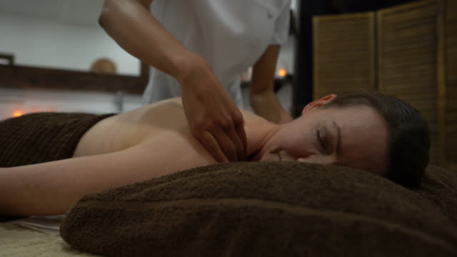friendly black masseuse giving a nice back massage to female customer at the spa - massage table stock videos & royalty-free footage