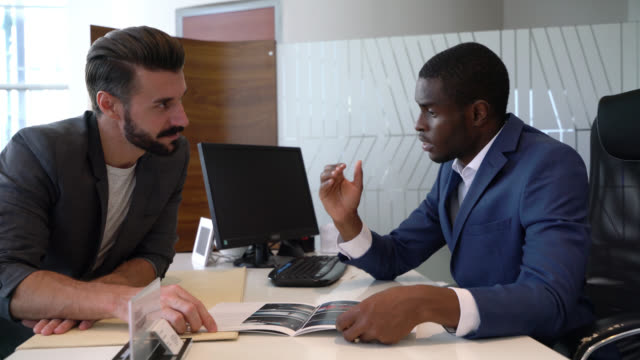friendly black sales man at a car dealership showing a catalogue to caucasian customer while explaining something - sale stock videos & royalty-free footage