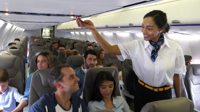 friendly black stewardess turning off the button while talking to female passenger to help her with something - abitacolo video stock e b–roll