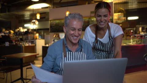 vídeos y material grabado en eventos de stock de dueño de negocio amistoso sobre algunos documentos y la información del restaurante con mujer gerente ambos feliz - pequeña empresa