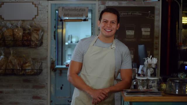 freundlicher geschäftsinhaber einer bäckerei, die sich lächelnd auf die kamera stützt - bäckerei stock-videos und b-roll-filmmaterial