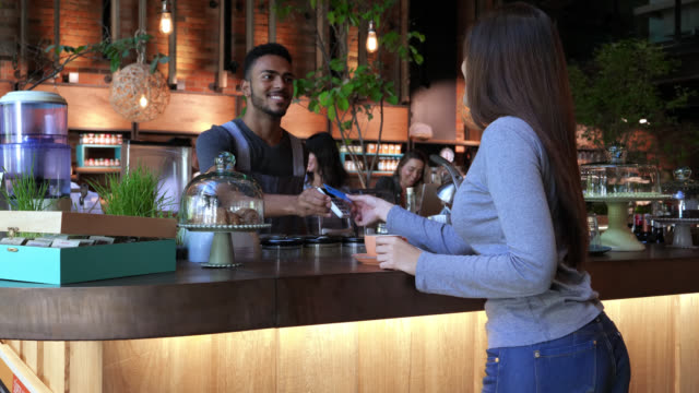 friendly business owner serving coffee to female customer who pays her order with credit card - bakery stock videos and b-roll footage