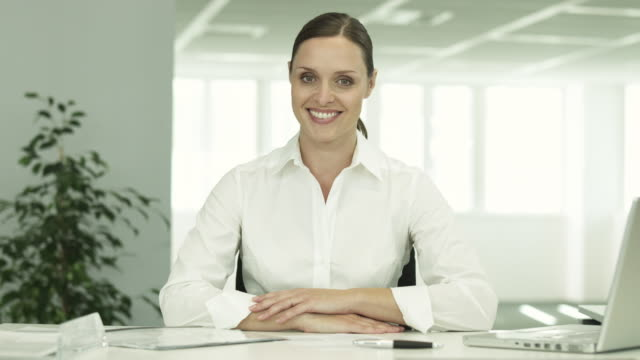 TS friendly businesswoman at desk smiles to camera
