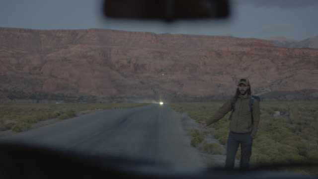 vidéos et rushes de friendly car stops to pick up young hitchhiker on scenic mountain backroad. - règle de savoir vivre