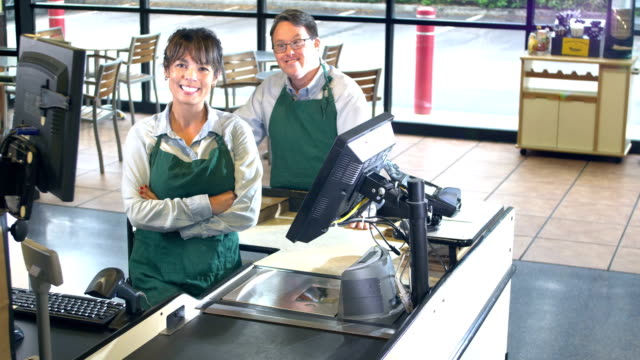 friendly cashier and bagger at supermarket checkout - bagger stock videos & royalty-free footage