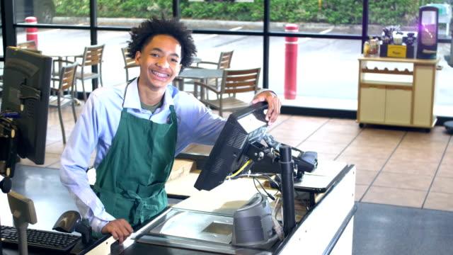 stockvideo's en b-roll-footage met vriendelijke kassier bij supermarket checkout - afro amerikaanse etniciteit