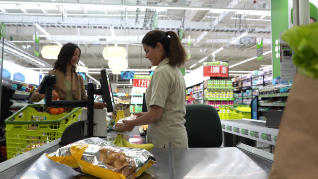 friendly cashier registering products with bar code reader at a supermarket checkout to female customer - cashier stock videos & royalty-free footage