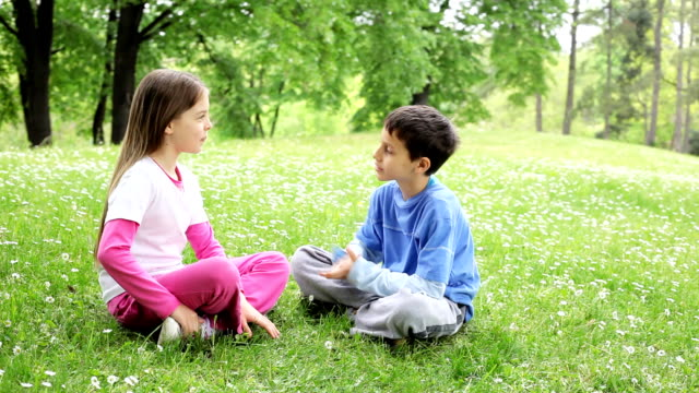friendly children discussing in the park. - children only stock videos & royalty-free footage