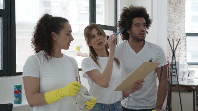 friendly cleaning supervisor assigning tasks to her team during a cleaning shift at an office while looking at her clipboard - clipboard stock videos & royalty-free footage