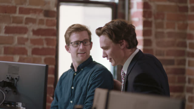 friendly colleague pats coworker on the back as he leaves the conversation - formal businesswear stock videos & royalty-free footage