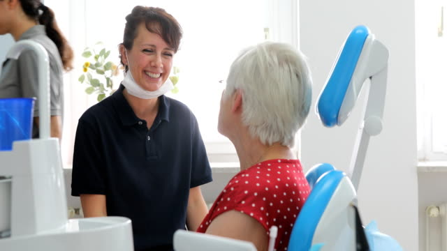 freundlicher zahnarzt im gespräch mit patientin in der klinik - zahnarzt stock-videos und b-roll-filmmaterial