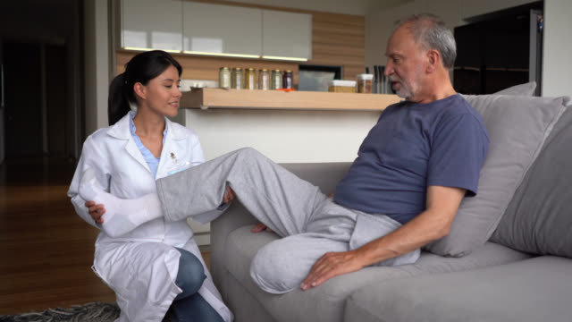 friendly doctor checking a disabled senior diabetic patient at his home - amputee stock videos & royalty-free footage