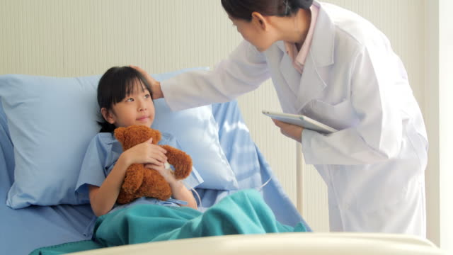 フレンドリーな医者は、かわいい女の子の定期検診を行います。中国・香港の医療システム - 怪我点の映像素材/bロール
