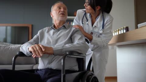 vänlig läkare på huset samtal kontrol lera en funktionshindrad senior patient på rullstol - besök bildbanksvideor och videomaterial från bakom kulisserna
