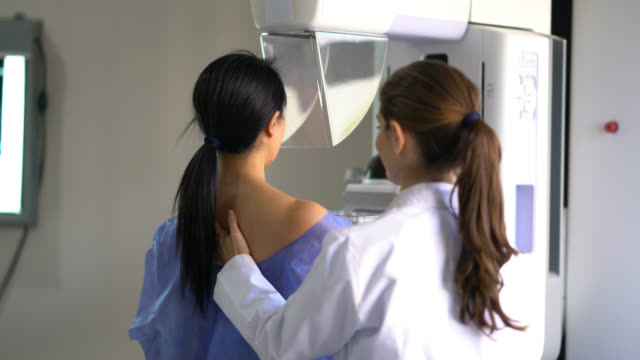 friendly doctor taking a mammography to a female patient - torso stock videos & royalty-free footage