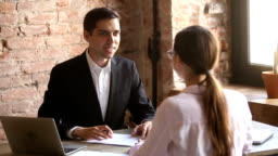 Friendly employer handshaking welcoming hired employee after successful job interview