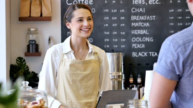 Friendly female barista helps male customer in cafe