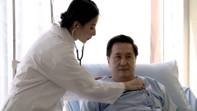 stockvideo's en b-roll-footage met vriendelijke vrouwelijke arts controleert op de zieke senior mannen patiënt in bed liggen - men