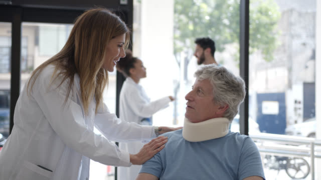 vídeos de stock, filmes e b-roll de médico amigável falando com paciente sênior do sexo masculino usando uma cinta no pescoço e sentado em cadeira de rodas no hospital - civil
