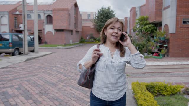 vídeos de stock, filmes e b-roll de amiga da vizinha saindo de casa para o trabalho e recebendo um telefonema no smartphone - mochila bolsa