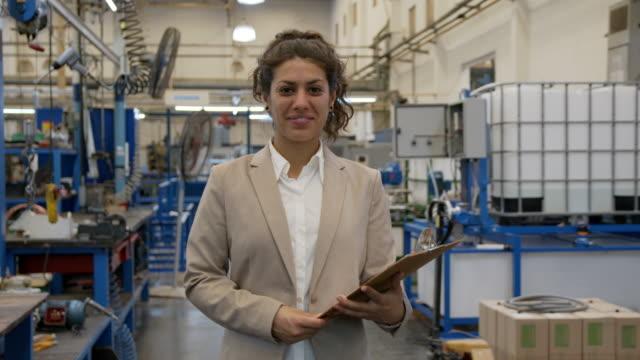 freundliche weibliche supervisor in einer fertigungsfabrik hält eine zwischenablage lächelnd fröhlich vor der kamera - kraftwerk stock-videos und b-roll-filmmaterial