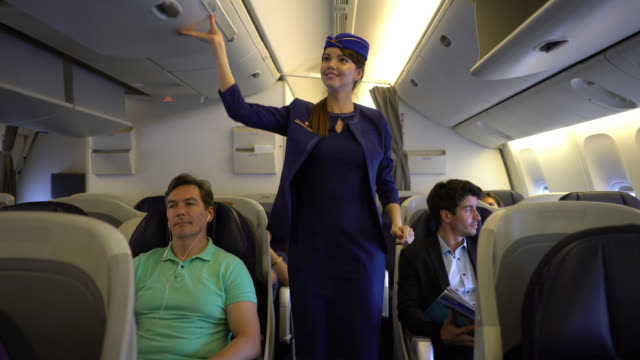 friendly flight attendant closing the over head compartments ready to take off walking down the aisle checking - crew stock videos & royalty-free footage