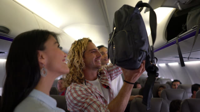 friendly flight attendant gesturing passengers where their seat is and couple looking very happy - abitacolo video stock e b–roll