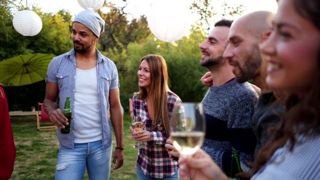freundliche gruppe von menschen, die spaß an einer party haben - vorlesen stock-videos und b-roll-filmmaterial