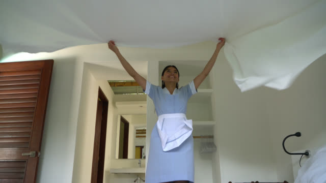 vídeos de stock e filmes b-roll de friendly hotel maid making the bed at a hotel - hóspede
