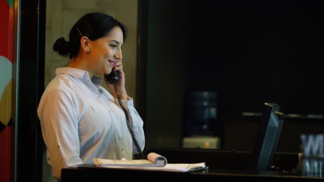 vídeos de stock, filmes e b-roll de recepcionista amigável do hotel que responde a um atendimento de telefone na recepção - recepcionista