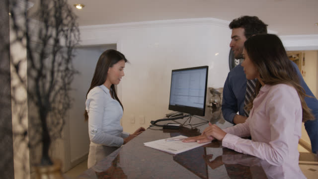friendly hotel receptionist handing a key card to business couple who just checked in to hotel - checkout stock videos & royalty-free footage