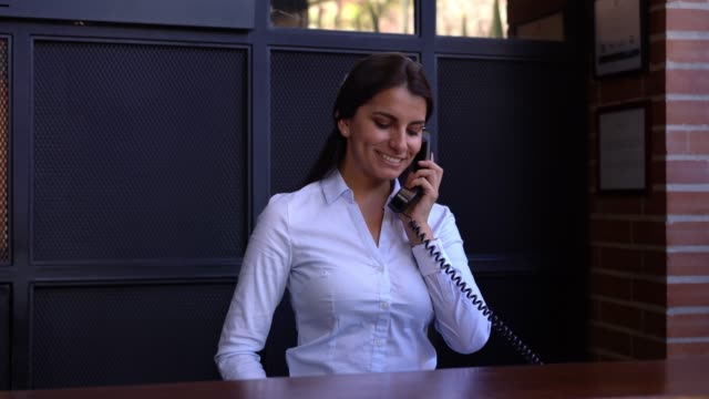 friendly hotel receptionist on a phone call with a guest smiling - guest stock videos & royalty-free footage