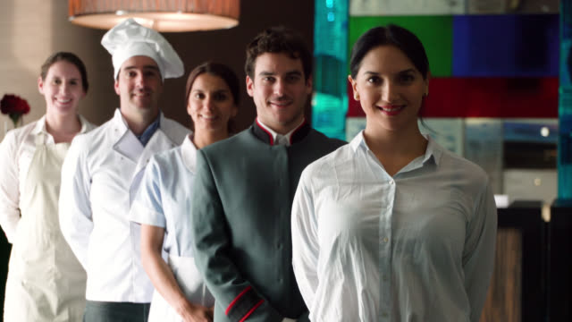 friendly hotel staff all standing behind hotel manager in a line smiling at camera - waiter stock videos & royalty-free footage