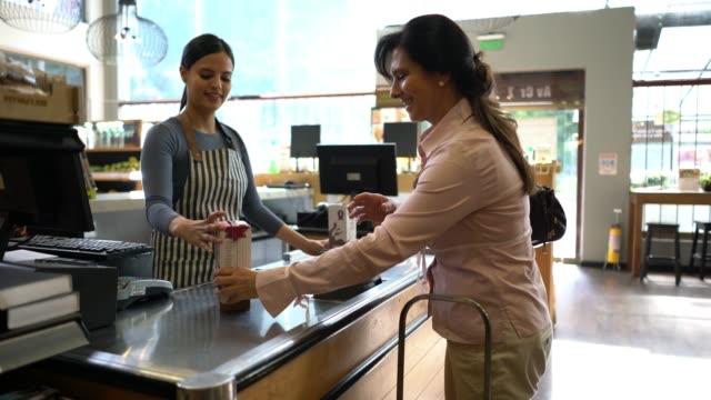 フレンドリーなラテン アメリカ レジ女性客の食料品店でチェック アウトを助ける - レジ係点の映像素材/bロール
