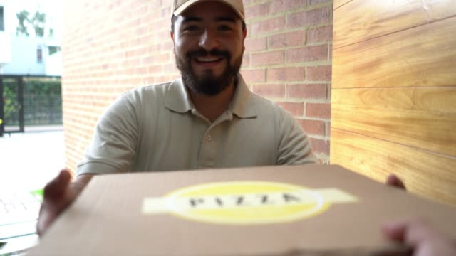 friendly man delivering a pizza to customer at home smiling - receiving stock videos & royalty-free footage