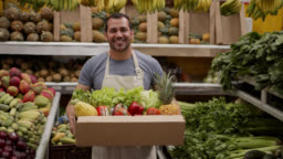 Friendly man preparing a delivery for customer in a cardboard box full of fresh fruits and vegetables looking at camera smiling