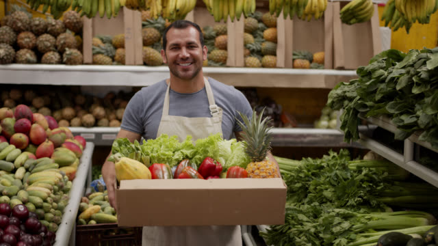 friendly man preparing a delivery for customer in a cardboard box full of fresh fruits and vegetables looking at camera smiling - market trader stock videos & royalty-free footage