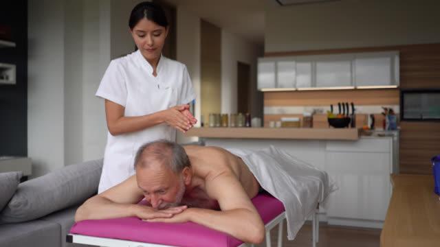 freundliche masseurin massiert einen älteren zu hause - hausbesuch stock-videos und b-roll-filmmaterial