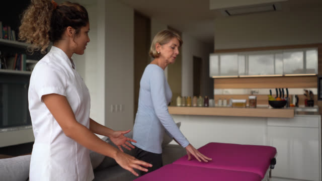 friendly masseuse ready to service a senior woman patient at home both smiling - osteopath stock videos & royalty-free footage