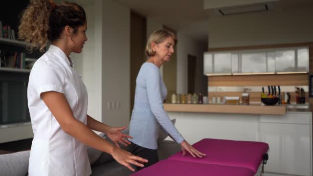 vidéos et rushes de masseuse amicale prête à servir un patient aîné de femme à la maison souriant - kinésithérapie