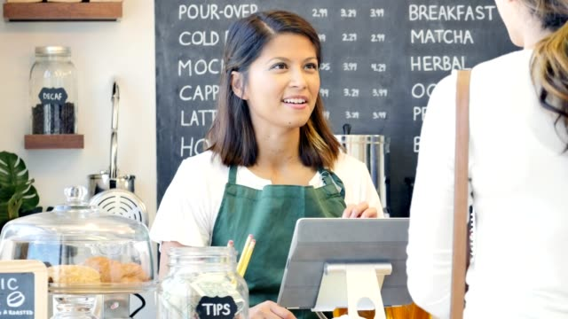Friendly mid adult Asian female barista assists female customer with her order