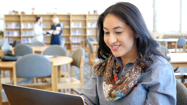 Friendly mid adult Hispanic woman using computer in modern college library during study session