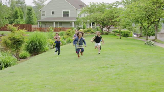 vídeos de stock, filmes e b-roll de simpático bairro crianças brincando juntos ao ar livre - brincadeira de pegar
